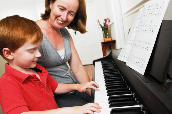Little boy taking piano lessons