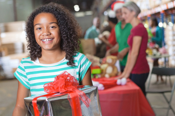 Little girl giving a present at a donation center