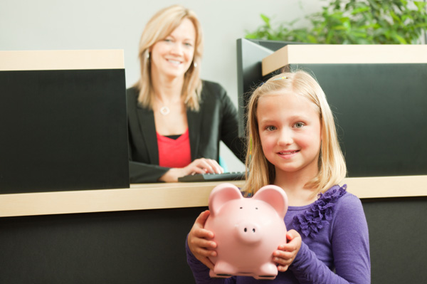 Child with piggy bank at bank