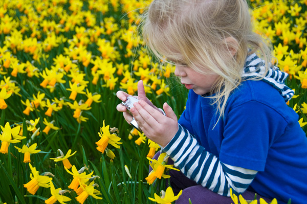 Little girl taking photos of nature