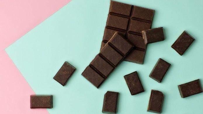 Dark chocolate bar pieces on pink