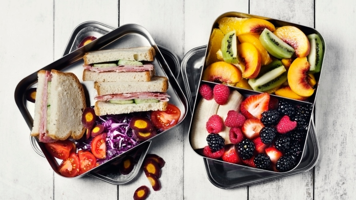 Two lunch boxes with sandwiches, veggies