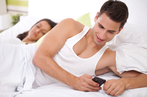 Man texting while in bed with woman