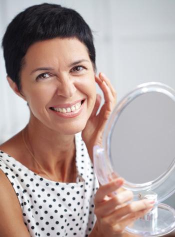 Mature woman applying makeup