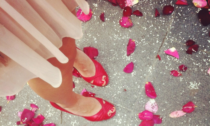Woman feet and rose petals on