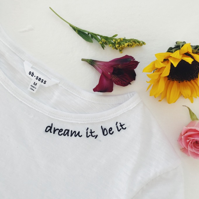 White shirt with text on it surrounded by flowers