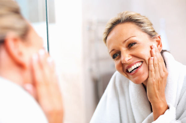 middle aged woman looking in mirror