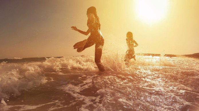 Girls running into the water on