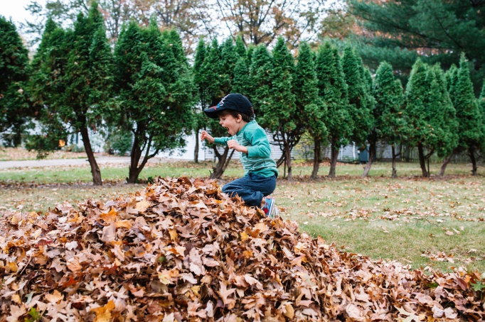 Boy jumping in fall leaves