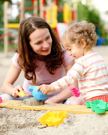 mom and daughter playing in sandbox
