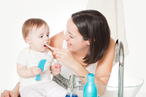 Mom brushing baby teeth