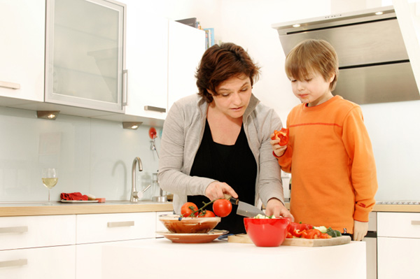 Mom chopping veggies with son