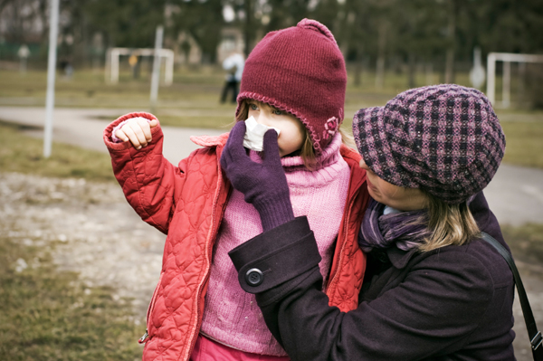 Mom covering nose of child