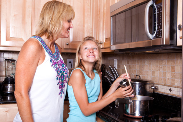 Mom and daughter cooking soup
