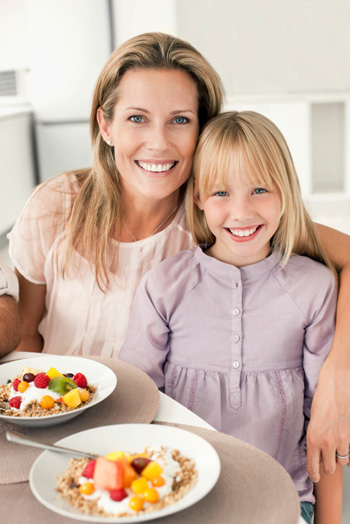 Mom and daughter eating healthy breakfast