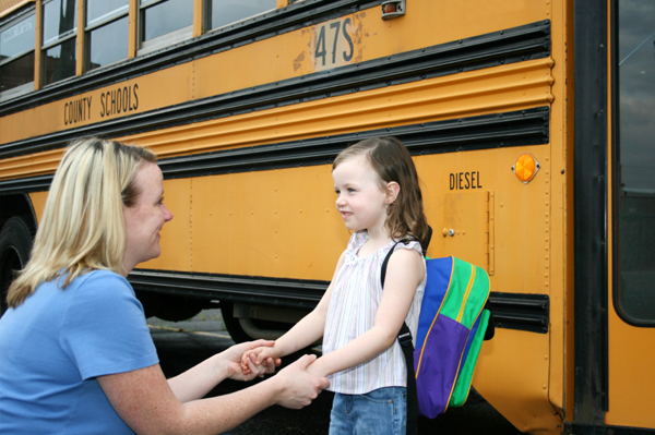 Mom dropping off daughter at school bus