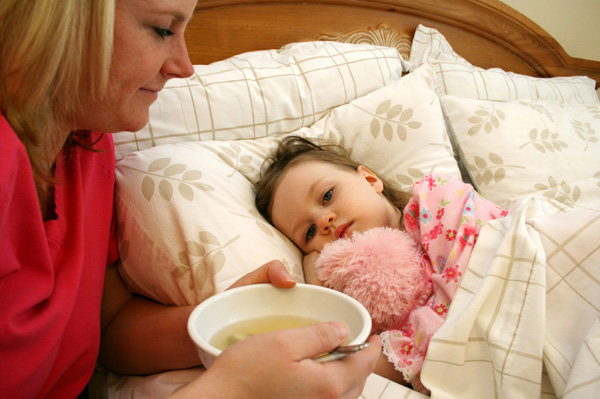 Mom giving sick child soup