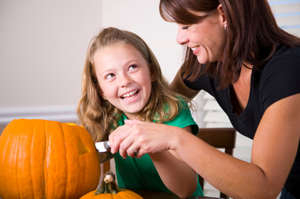 Mother helping daughter carve pumpking