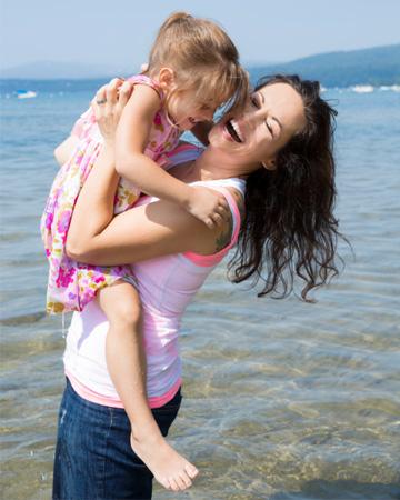 Mom holding daughter in lake