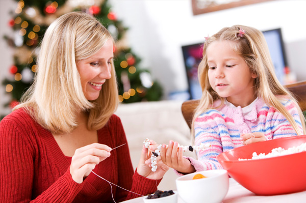 Mom making popcorn garland with daughter