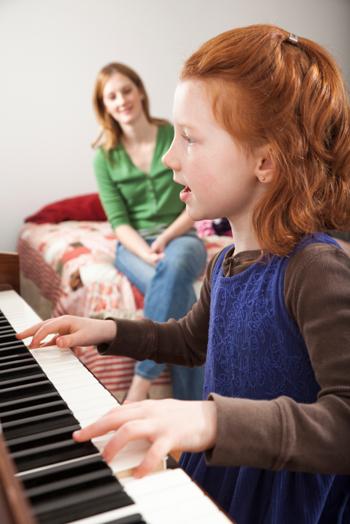 Mom watching daughter play piano