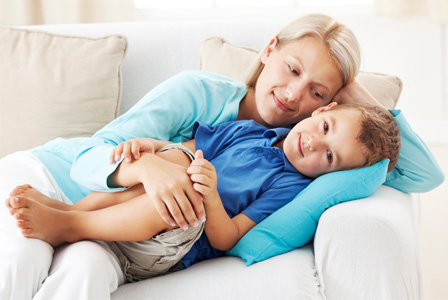 Mother holding son on couch