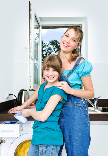 Mom teaching daughter to do laundry