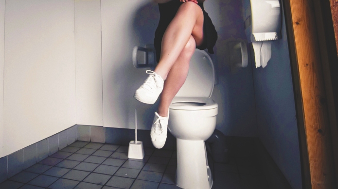 Woman Sitting Over Commode At Public