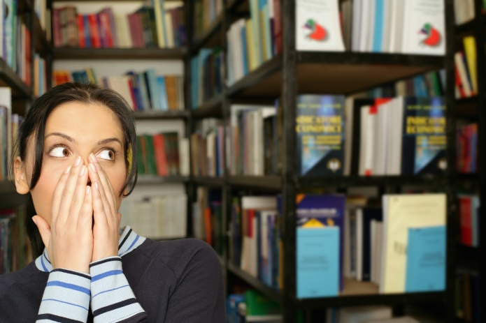 Shocked young woman in library