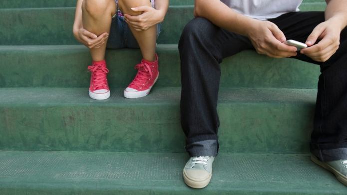 Teenage couple sitting together on steps