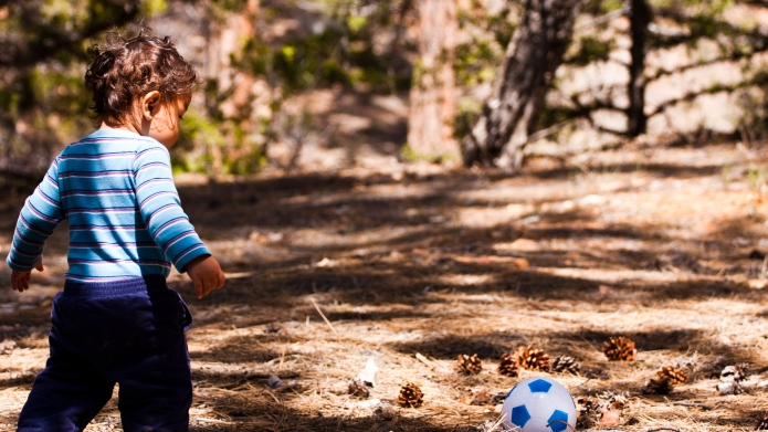 Toddler child with soccer ball kicking