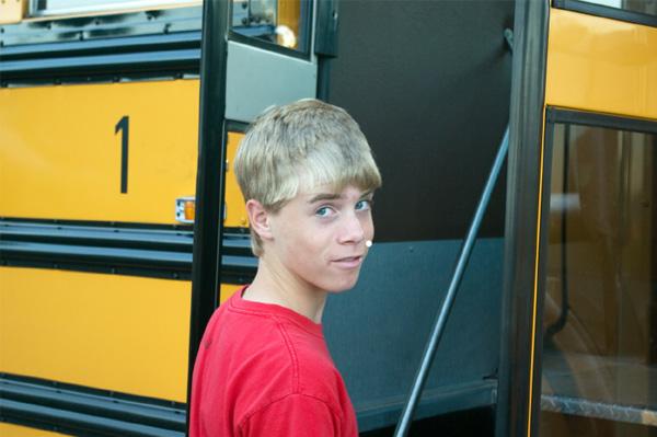 Nervous teen boy getting on bus