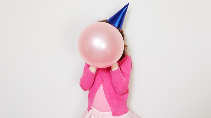 Girl holding pink balloon in front