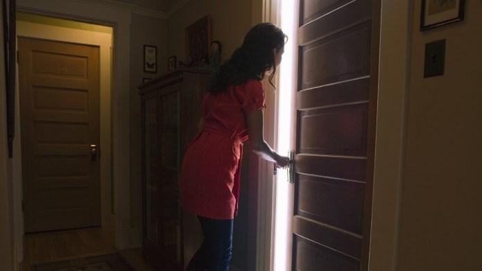 Woman opening bedroom door with light