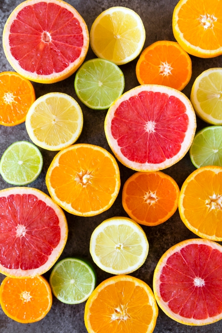 A variety of citrus fruits, cut in half.