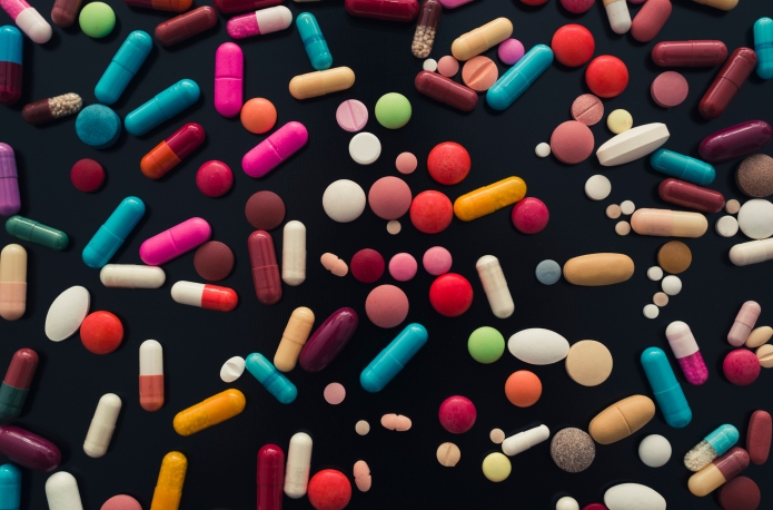 hundreds of colorful pills on black
