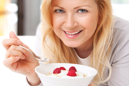 Older woman eating yogurt and fruit in bed