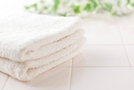 Organic bath towels on white tile