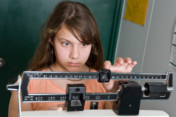 Overweight teen on scale