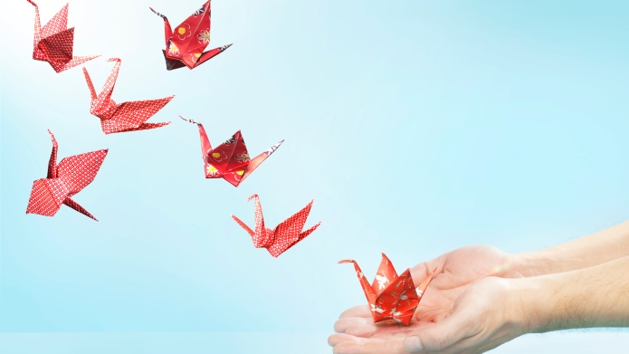 Red origami cranes flying away from