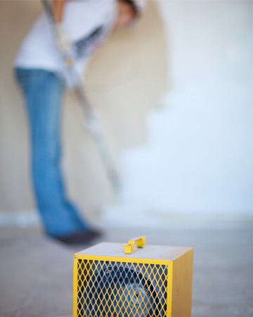 Man painting damp wall