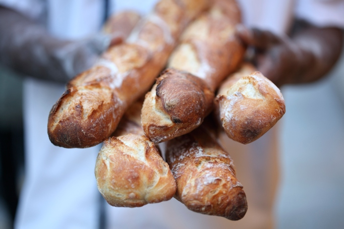 A baker holding baguettes