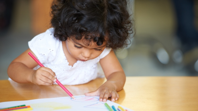 A cute little girl drawing a
