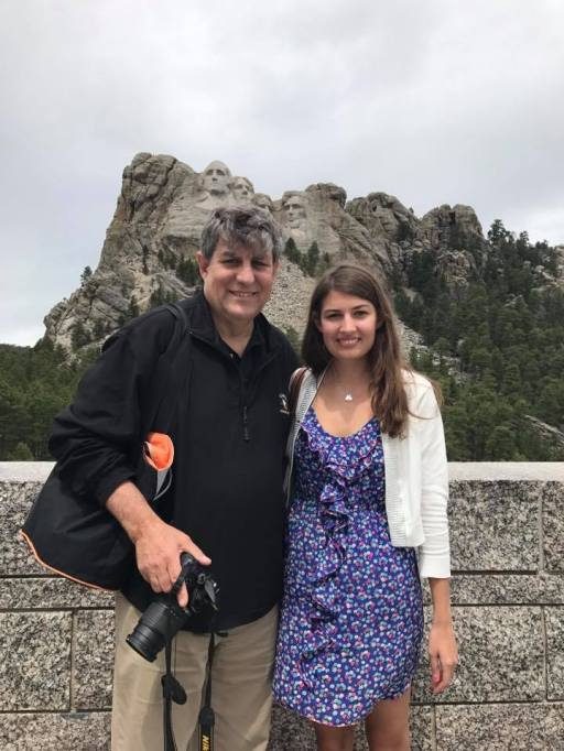 Father and daughter standing in front of mountains