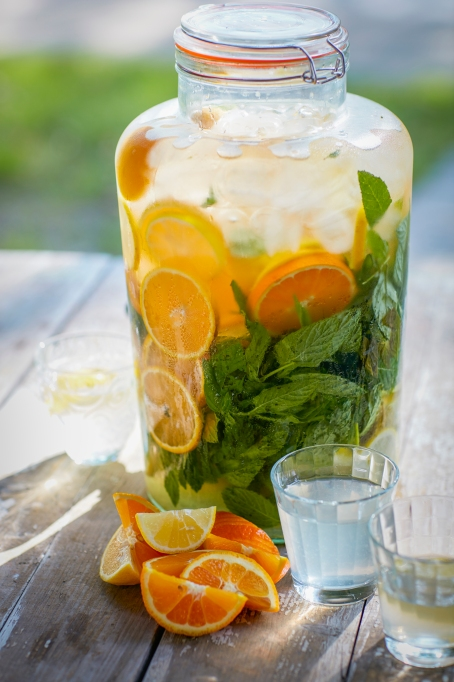 Water with orange slices and a herb.