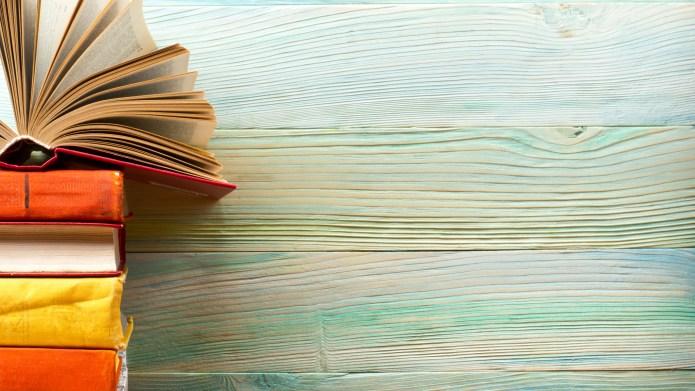 Open book, hardback books on wooden