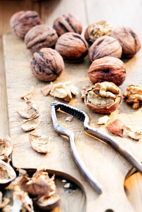 Walnuts and a nutcracker on a cutting board.