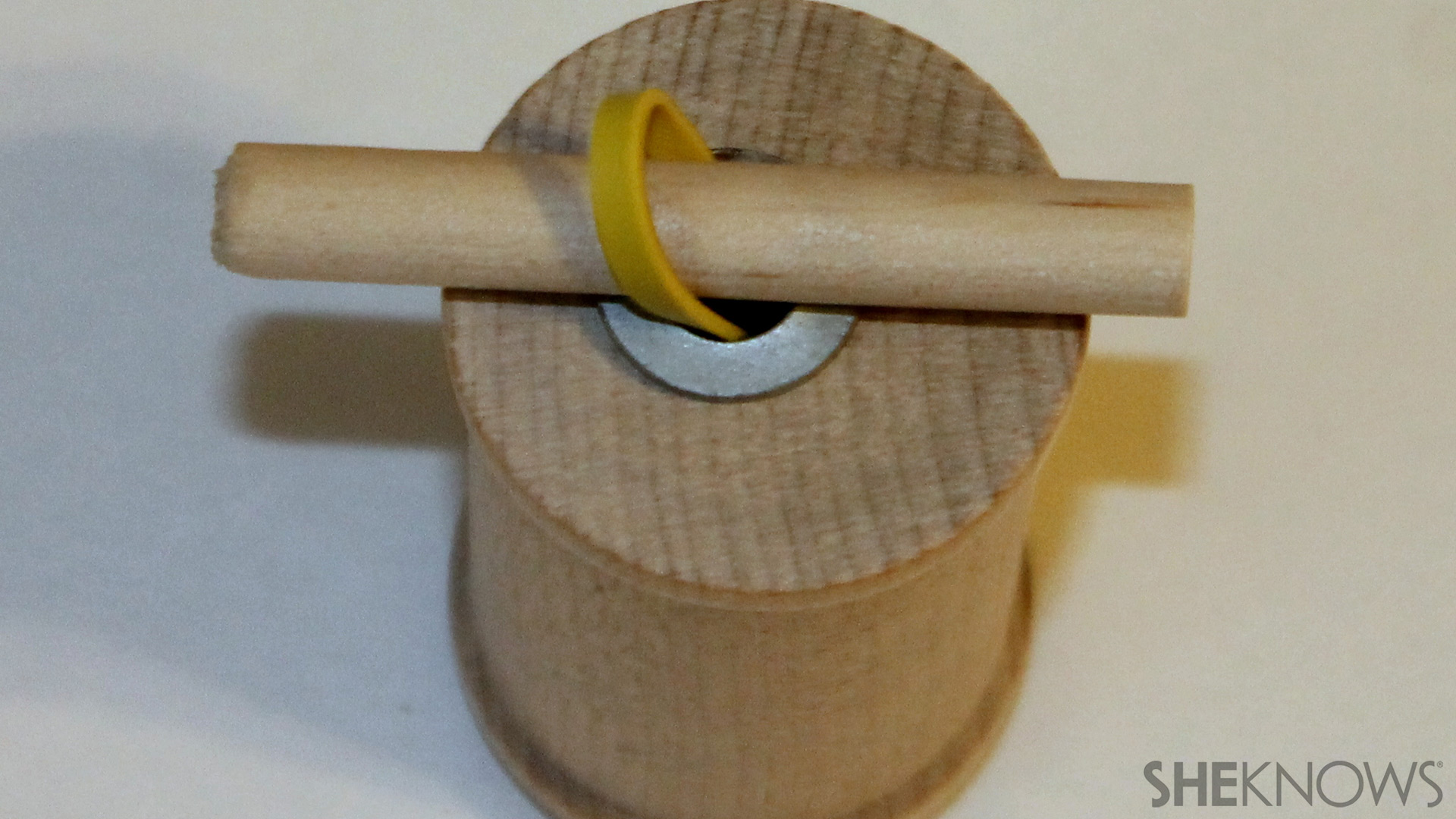 Thread a dowel through the loop of the rubber band