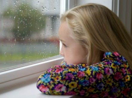 Bored girl looking out the window on a rainy day