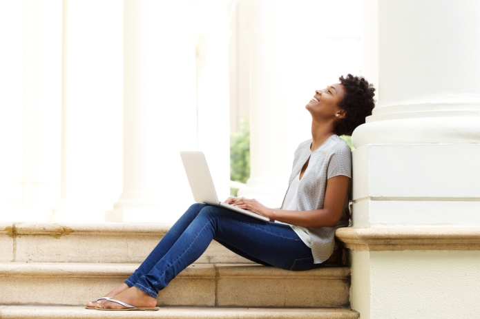 Relaxed young african woman sitting outside